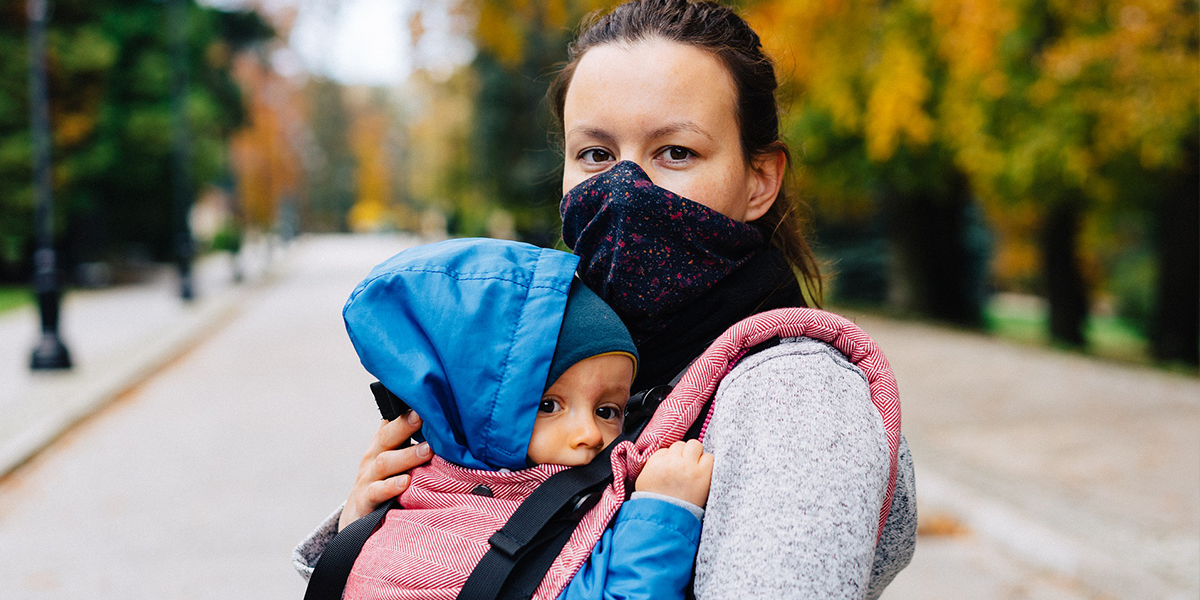 Woman with face covering holding baby